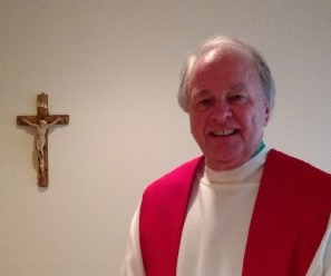 A portrait of Fr Larry Hansen dressed in white alb and red stole next to a crucifix